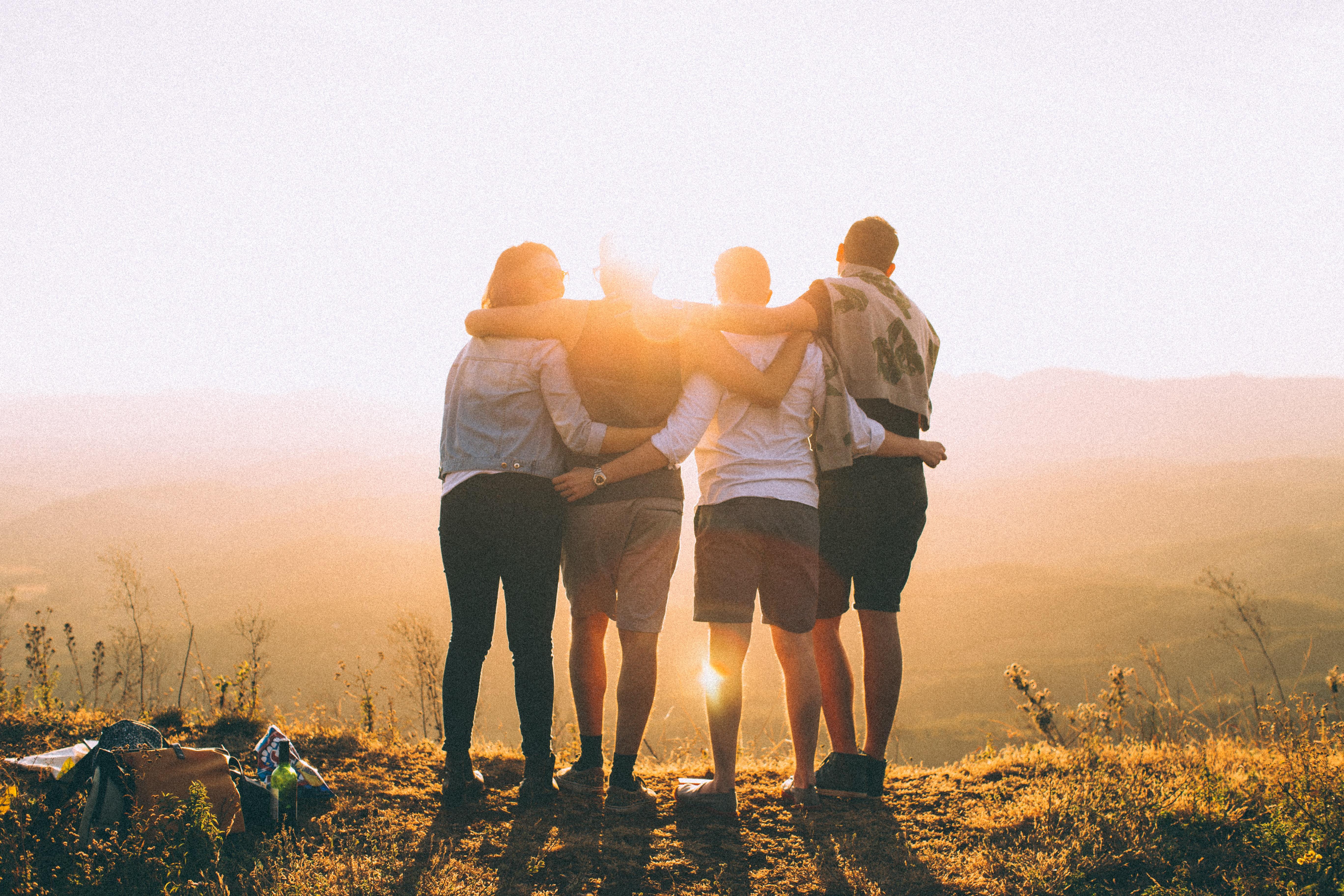 Fyra personer som håller om varandra och blickar ut mot ett berg.
