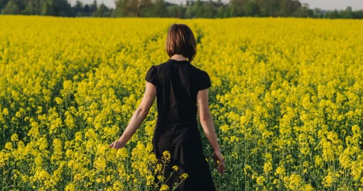 Kvinna som går i rapsfält.