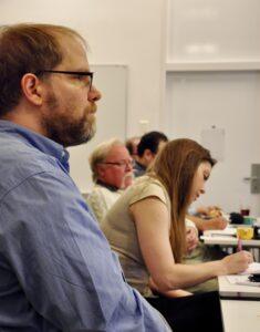 Deltagare från Funktionsrätt Skåne, en man och en kvinna. Mannen till vänster lyssnar intresserat på presentationen och kvinnan intill antecknar.