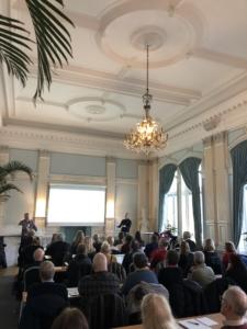 Bild från sal i Börshuset där ett 50 tal deltagare syns bakifrån och Stefan Johansson, Begripsam presenterar längst fram.