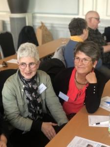 Två kvinnor diskuterar leende med en tredje part som ej syns i bild.