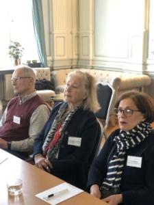 Tre deltagare som lyssnar på dagens presentationer. Från vänder sida en  man med grått hår, en ljushårig kvinna i mitten och en mörkhårig kvinna med glasögon till höger.