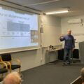 Bilden visar Greger Linander presentera en powerpoint.